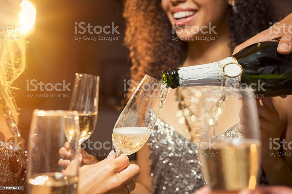 Pouring champagne at party stock photo