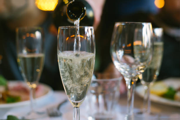 pouring champagne into a glass stock photo