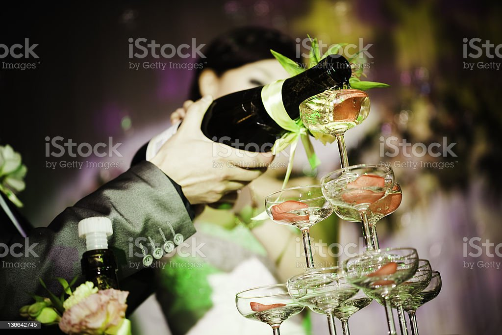 pouring champagne into glass at wedding royalty-free stock photo