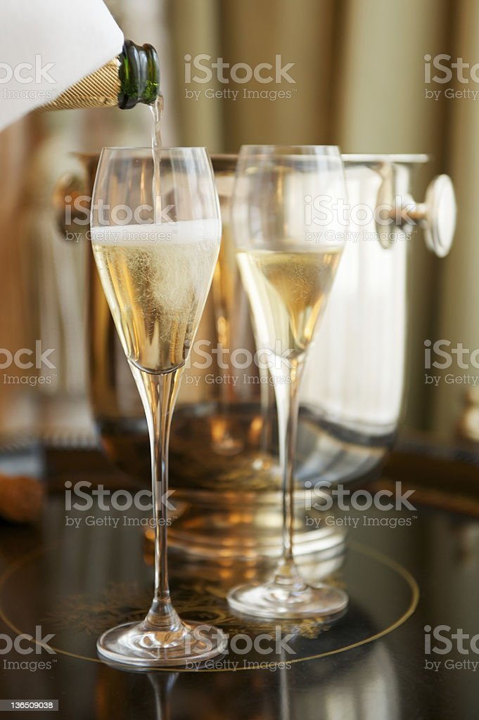 Pouring champagne into two glasses from bottle wrapped in napkin stock photo