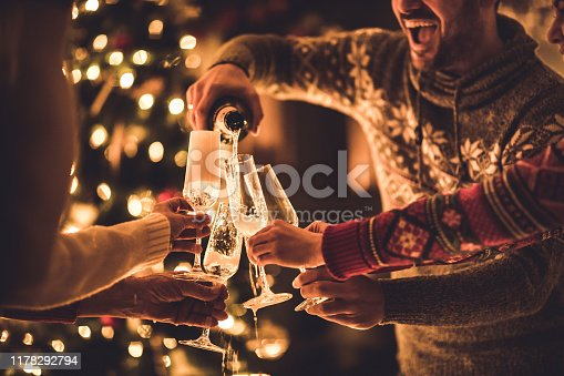 Group of unrecognizable people pouring champagne from a bottle on New Year's party.