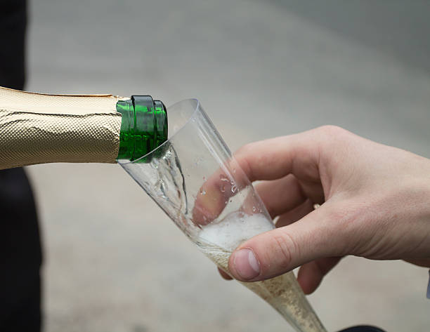 Pouring Champagne to Disposable Cup stock photo