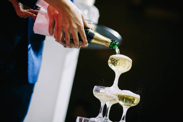 Pouring Champaign into glasses tower in wedding reception Pouring Champaign into glasses tower in wedding reception by bride and bridegroom wedding asian night stock pictures, royalty-free photos & images