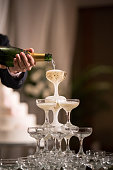 Pouring Champaign into glasses tower in wedding reception