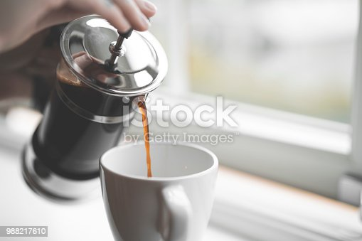French style coffee press filled with hot coffee on a white window sill inside a house in Sweden. Close-up shot with selective focus of a person with tattoos pouring coffee into a cup.