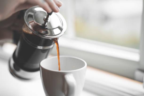 kaffee aus französischen presse auf fensterbank gießen - kaffeetasse tattoo stock-fotos und bilder