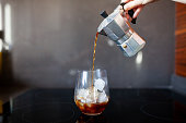 Pouring coffee from moka pot into glass with ice cubes stock photo
