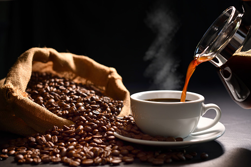 Pouring coffee with smoke on a cup and coffee beans on burlap sack on black background