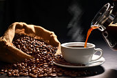 istock Pouring coffee with smoke on a cup and coffee beans on burlap sack on black background 1220101964