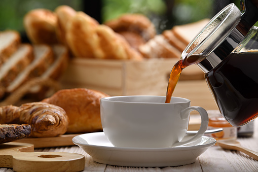 Pouring coffee with smoke on a cup with breads or bun, croissant and bakery on white wooden table