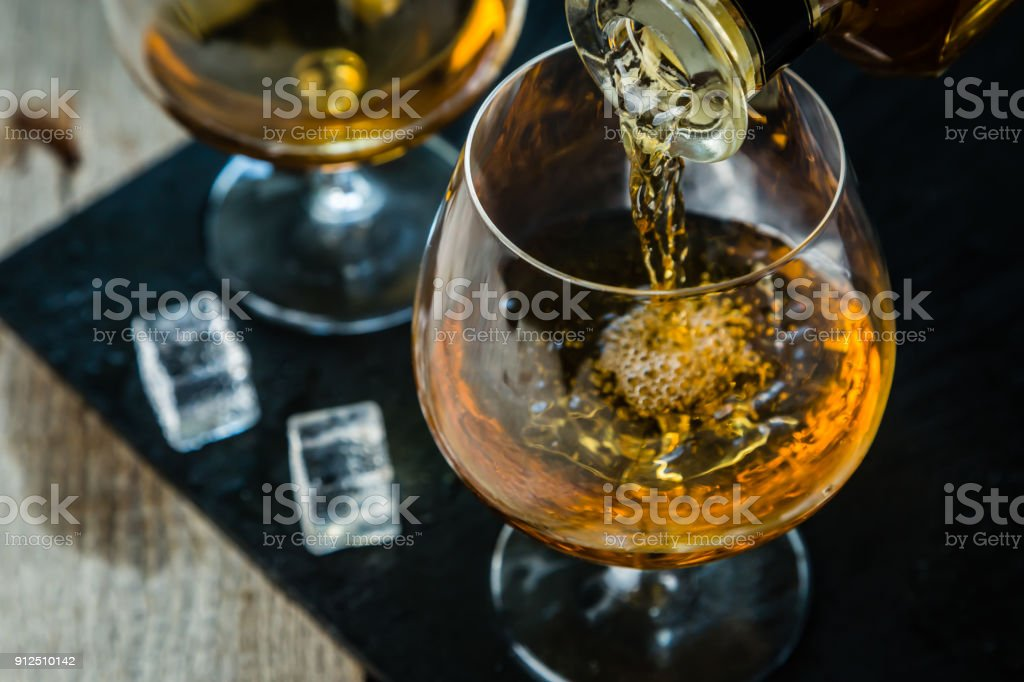 Pouring cognac in a glass stock photo