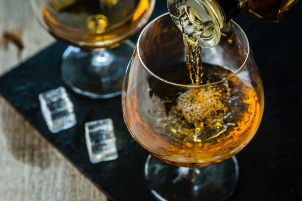Pouring cognac in a glass Pouring cognac in a glass, rustic background brandy stock pictures, royalty-free photos & images