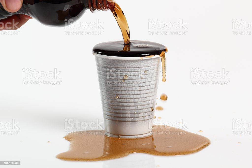 Pouring cola from plastic bottle into overflowing disposable cup stock photo