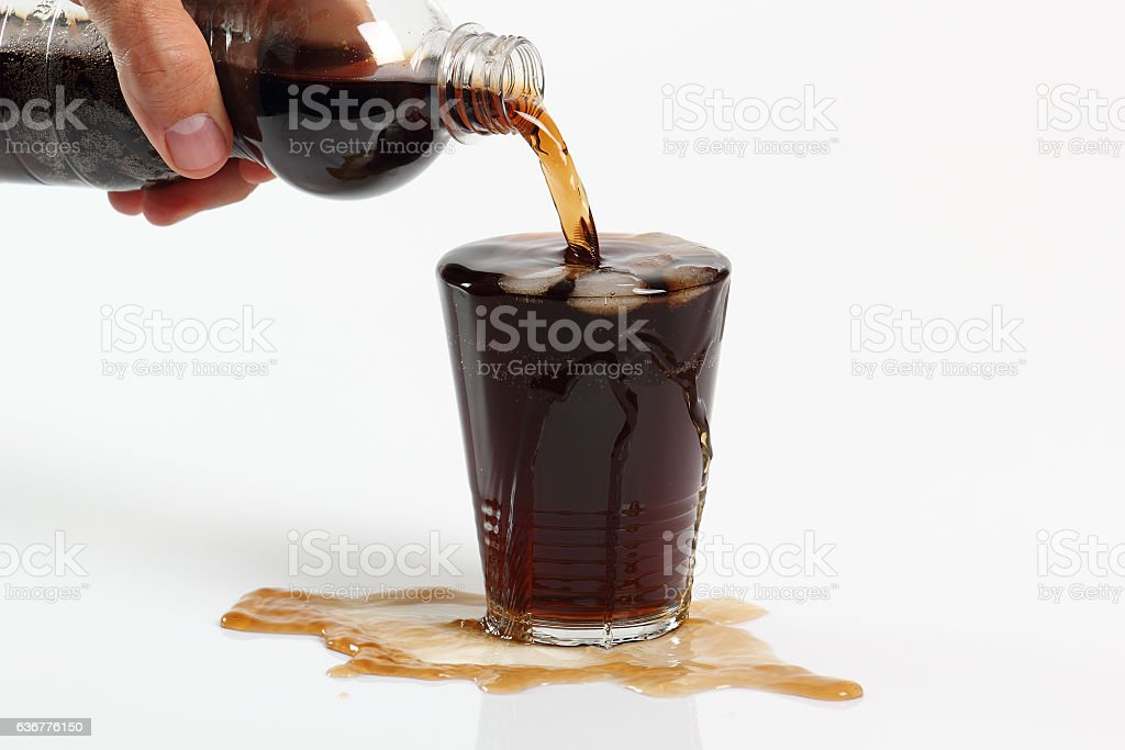 Pouring cola from plastic bottle into overflowing glass stock photo
