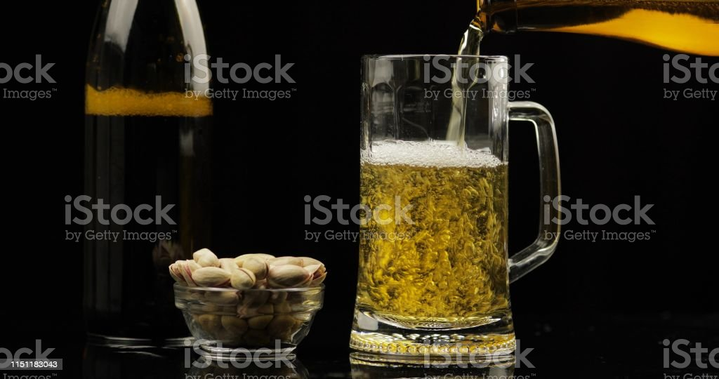 Pouring Cold Light Beer from bottle into a glass. Craft Beer...
