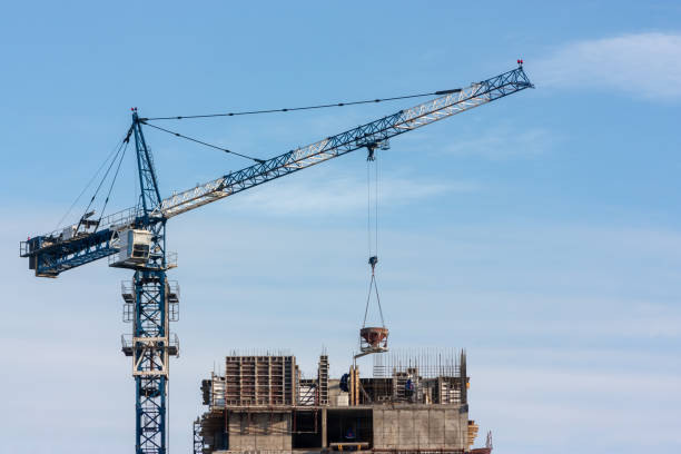 Pouring concrete into the formwork of a house under construction using a construction crane stock photo