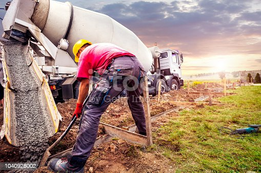 Pouring concrete to the foundations of the building. Construction Worker Guiding Cement Mixer Truck Trough. Cement Pouring from a Mixer Truck Chute. Concrete Foundation Construction.