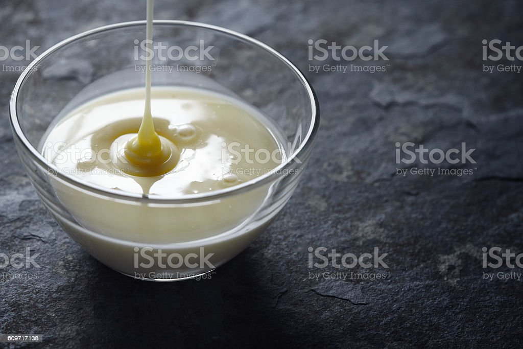 Pouring condensed milk in the glass bowl horizontal – Foto