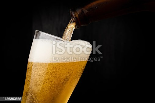 Pouring cool beer from bottle into glass on dark wood wall backgroud alcohol celebration concept
