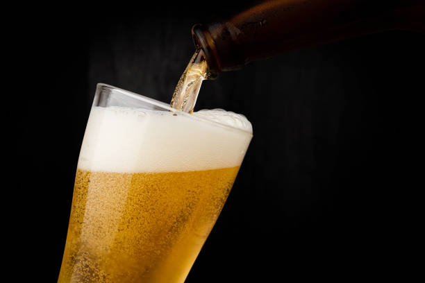 Pouring cool beer from bottle into glass on dark wood wall backgroud alcohol celebration concept stock photo