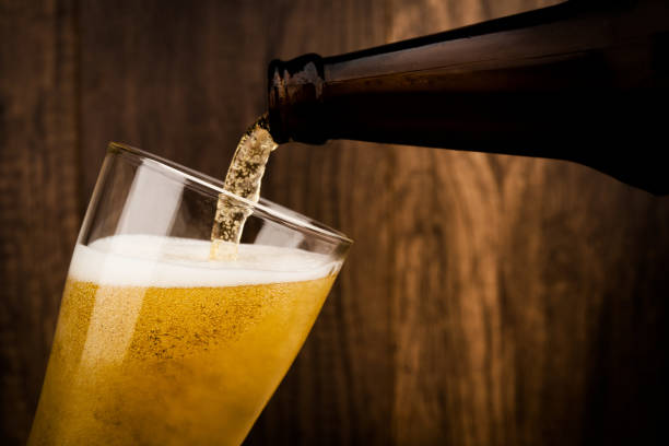 Pouring cool beer from bottle into glass on wood wall backgroud alcohol celebration concept stock photo