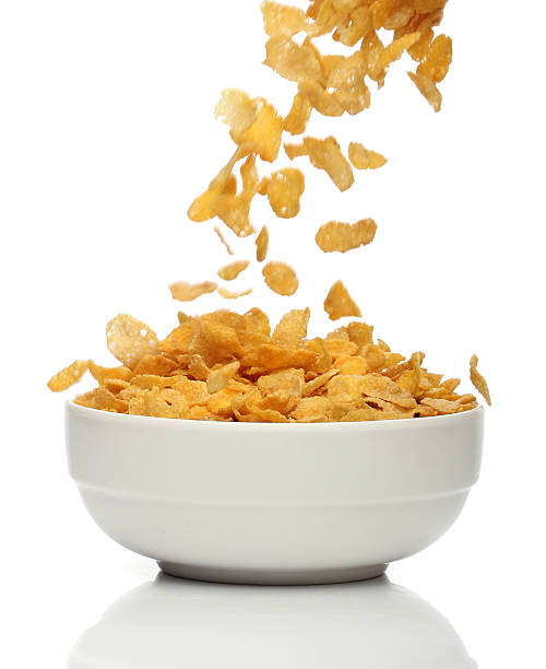 Pouring cornflakes into a bowl stock photo