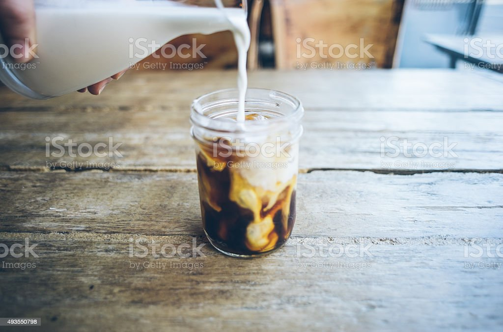 Pouring cream in cold brew coffee stock photo