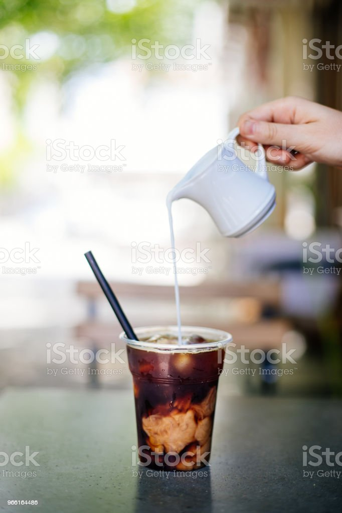 Pouring cream in cold brew coffee - Foto stock royalty-free di 2017