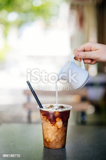 Pouring cream in cold brew coffee