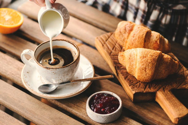 Pouring cream into black coffee Pouring cream into cup of black coffee. Tasty breakfast table set with croissants, jam and coffee coffee stock pictures, royalty-free photos & images
