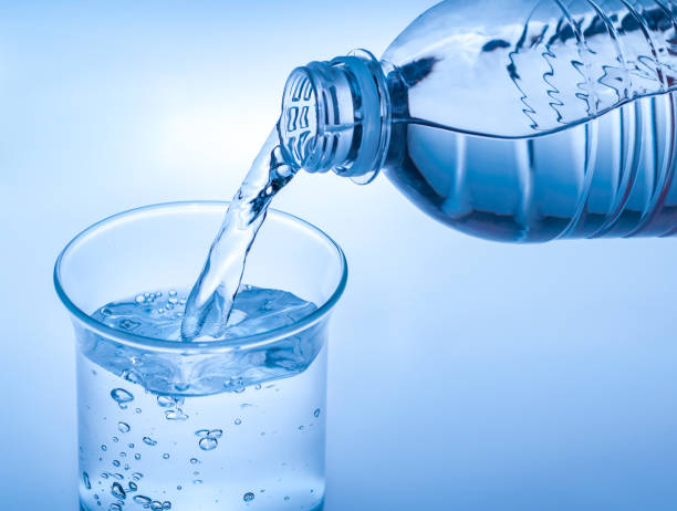Pouring crystal water from bottle on glass on blue background stock photo