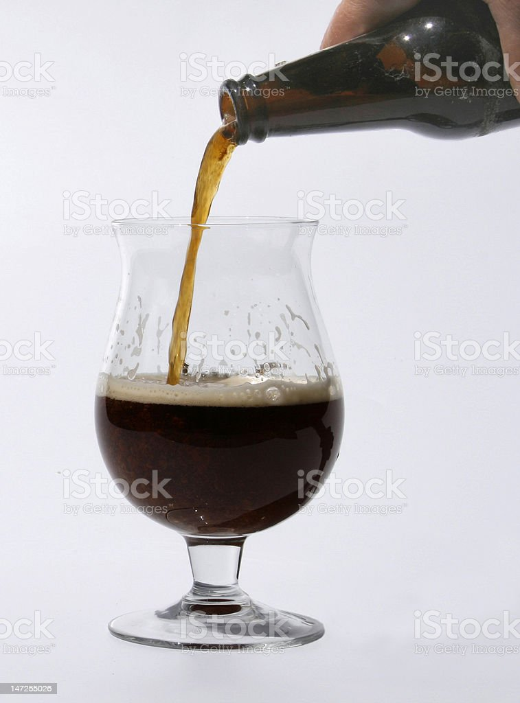 pouring dark beer into a glass stock photo