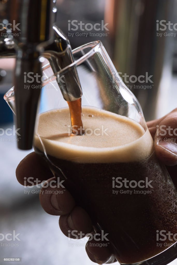 Pouring dark stout beer into glass stock photo