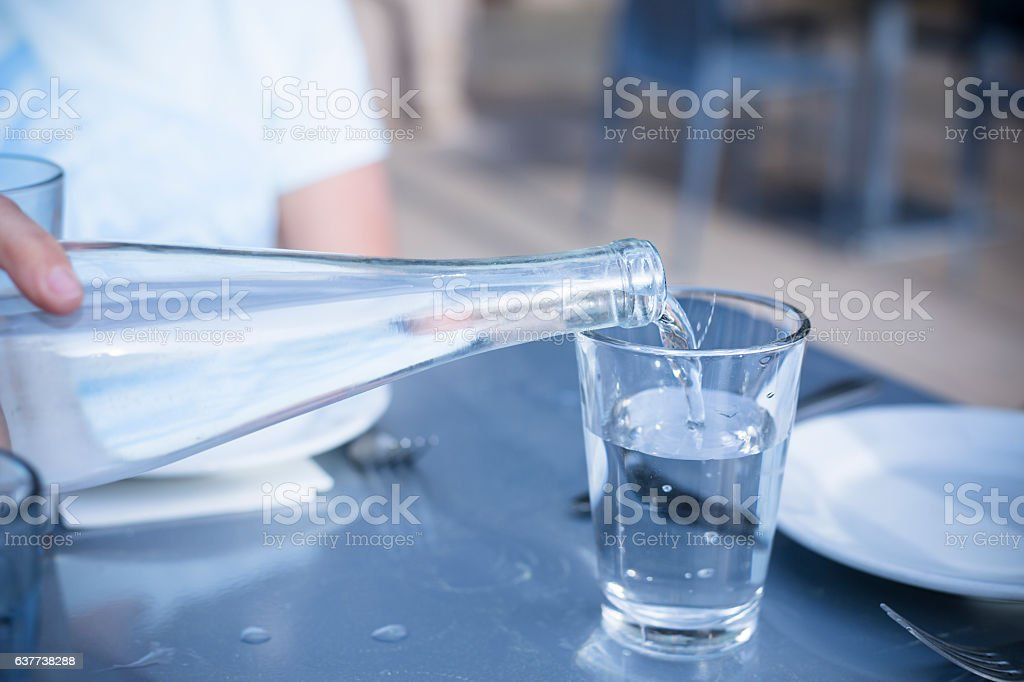 Pouring Distilled water into a clear glass at a restaurant stock photo