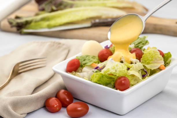 Pouring dressing on a salad. A studio image of a salad topped with cherry tomatoes and dressing being poured on it. salad dressing stock pictures, royalty-free photos & images