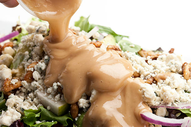 Pouring dressing over a salad human hand Pouring dressing over a salad salad dressing stock pictures, royalty-free photos & images