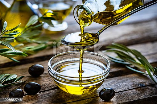Pouring extra virgin olive oil from a spoon to a glass container. Olive branches comes from the left and right. Some olive oil bottles are out of focus at background. Black olives are on the table and complete the composition. The composition is on a rustic wooden kitchen table. Predominant colors are gold, green and brown. High resolution 42Mp studio digital capture taken with Sony A7rII and Sony FE 90mm f2.8 macro G OSS lens