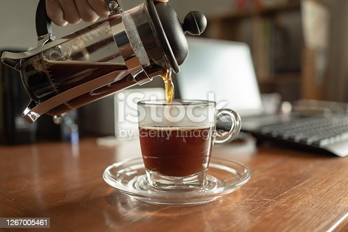 Pouring French press coffee into a cup on the working table at home