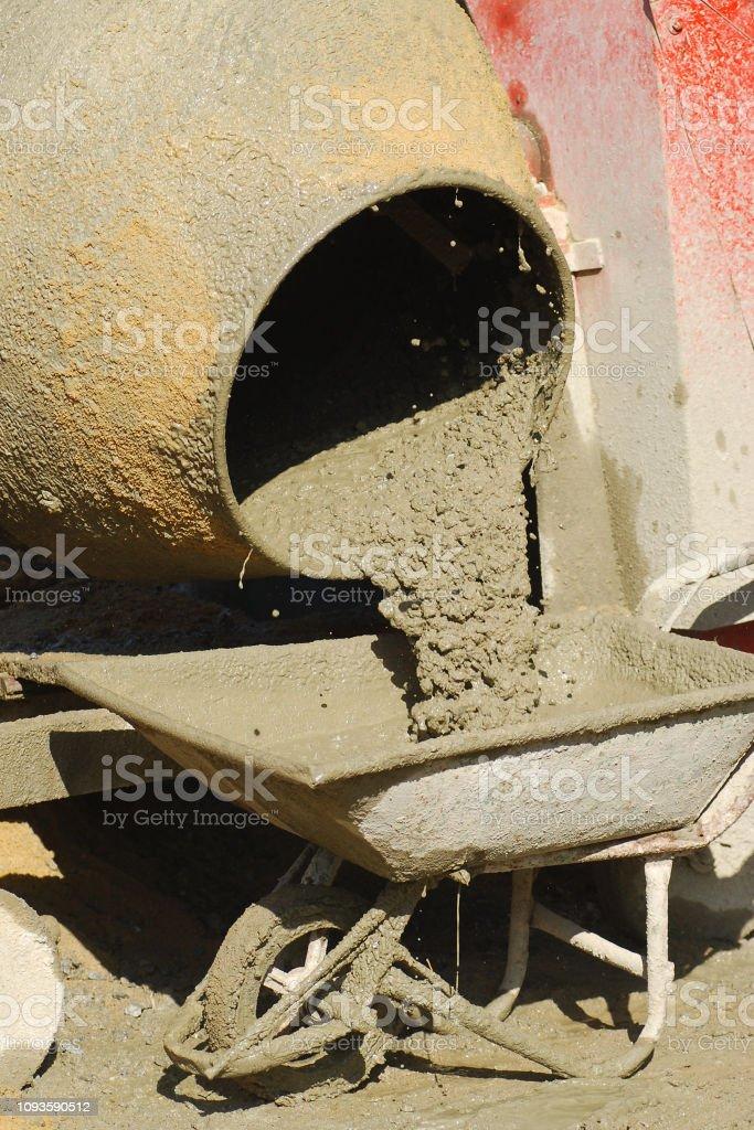Verter el hormigón fresco de la batidora eléctrica en carretilla - foto de stock