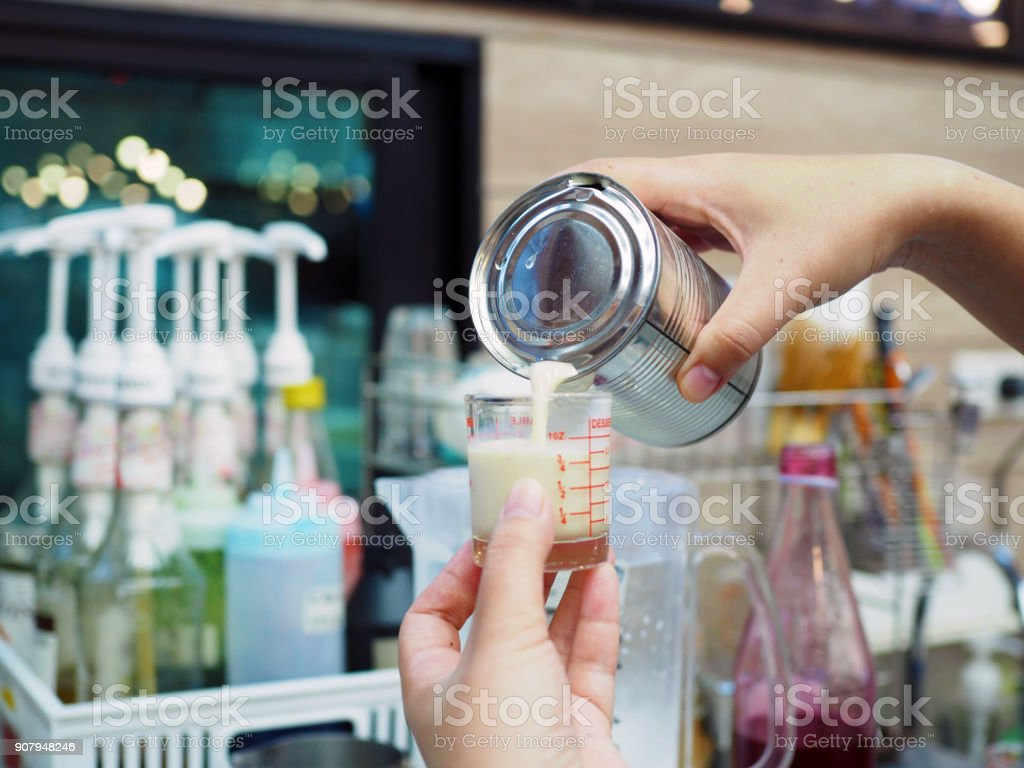 Pouring fresh milk from plastic jar to glass shot, prepared for iced latte. stock photo