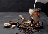 istock Pouring fresh milk into glass of iced black coffee on tray with beans and ground coffee with cane sugar and vintage shop on black background. 1279305474