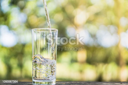 closeup Pouring fresh water on drinking glass over nature sunlight morning background