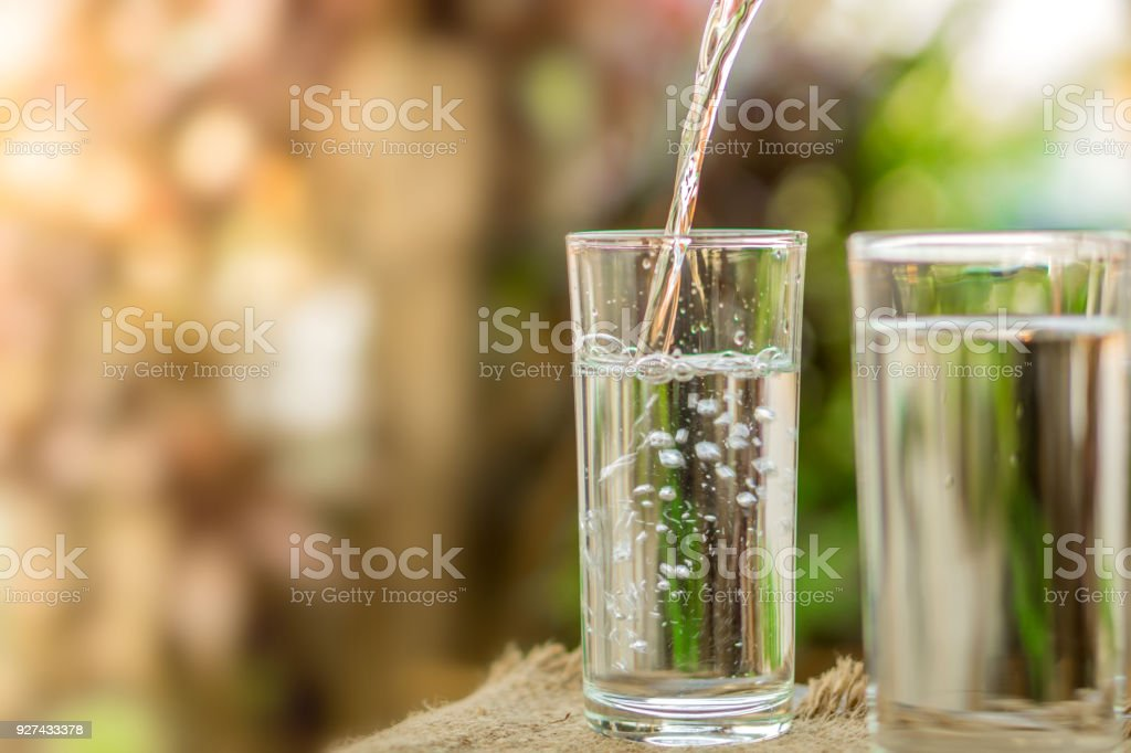 Pouring fresh water on drinking glass over nature sunlight morning background