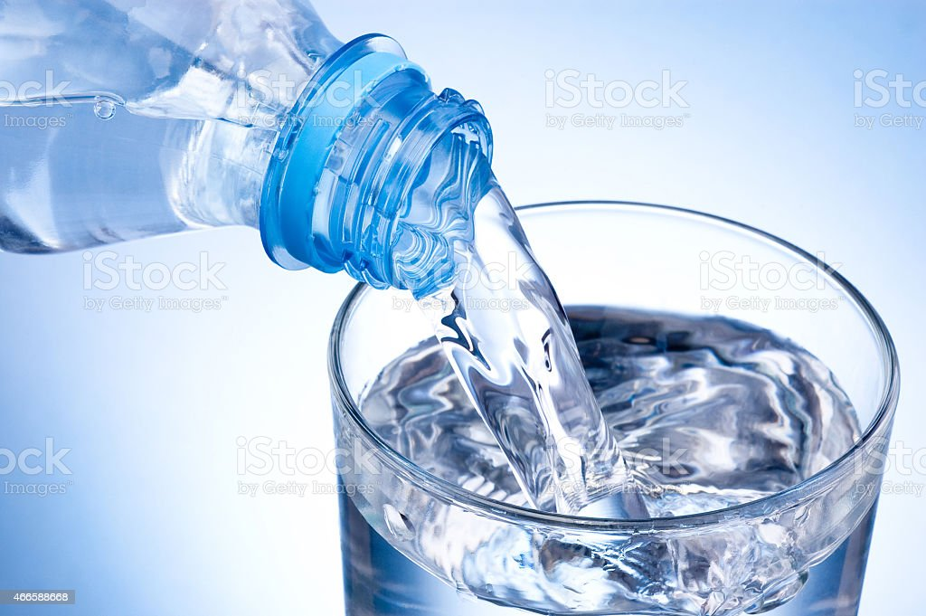 Pouring glass of water from plastic bottle on blue background stock photo
