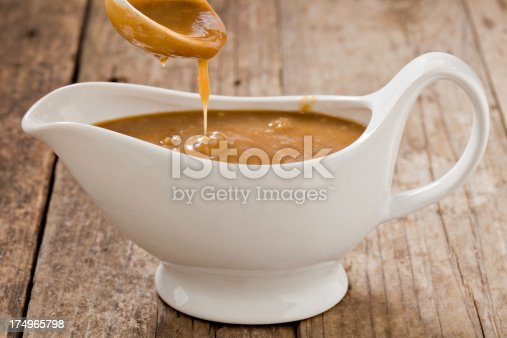 A close up shot of a small white ladle pouring brown gravy into a white ceramic gravy boat. Shot on a grungy old wooden table.