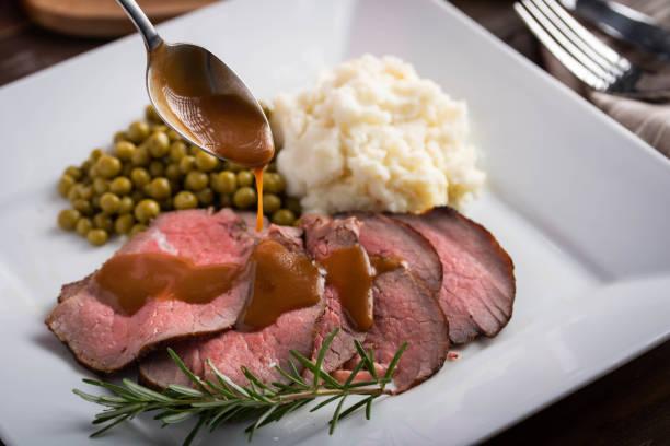 vertiendo salsa de salsa en rodajas de carne asada con patata sorda y guisantes dulces - rosbif fotografías e imágenes de stock