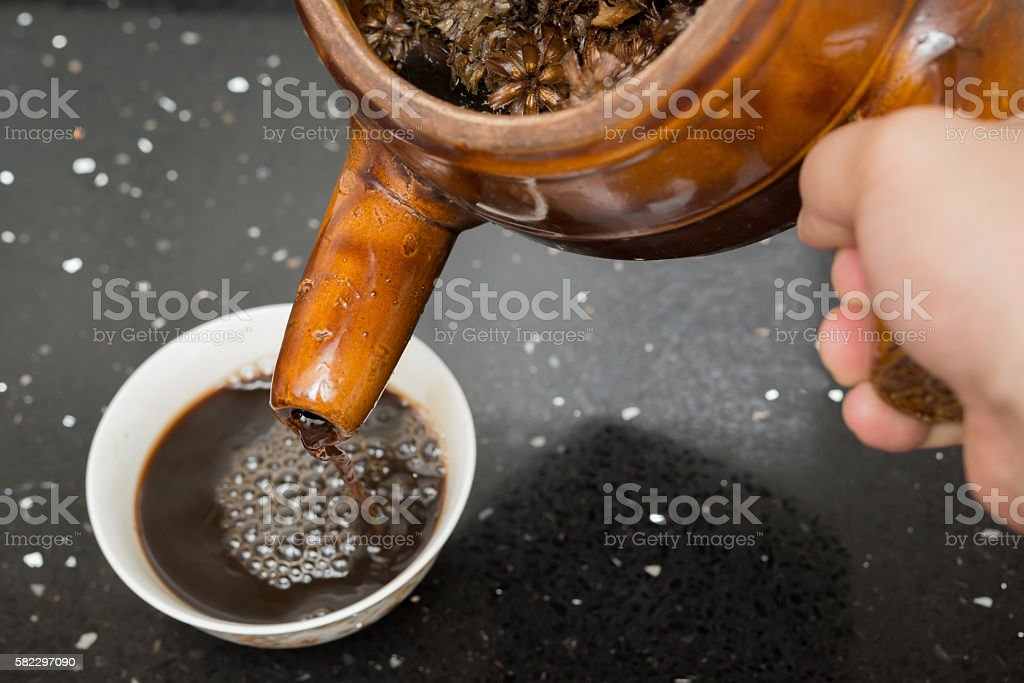 pouring herbal tea to a bowl stock photo