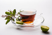 pouring Holy Basil or Tulsi Tea in transparent glass cup with saucer over white or black background. Popular Ayurvedic medicine from India