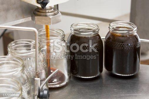 Pouring organic honey into storage glass jars.