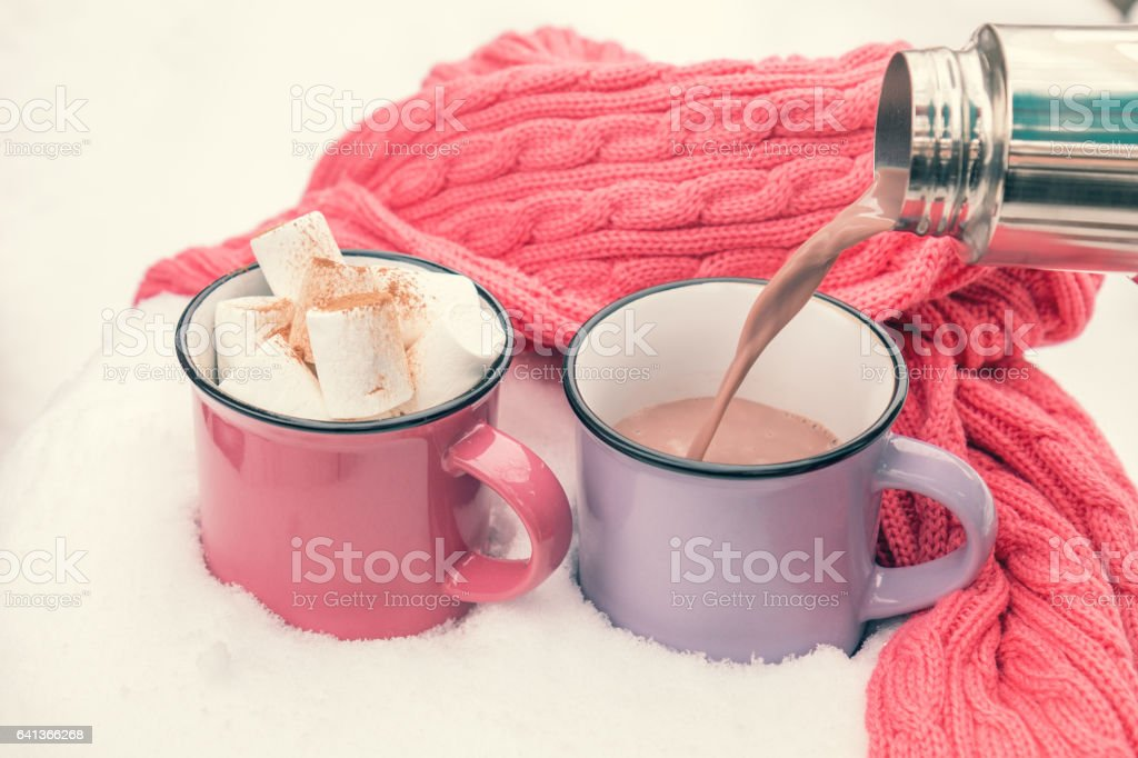 Pouring hot chocolate in the cup stock photo